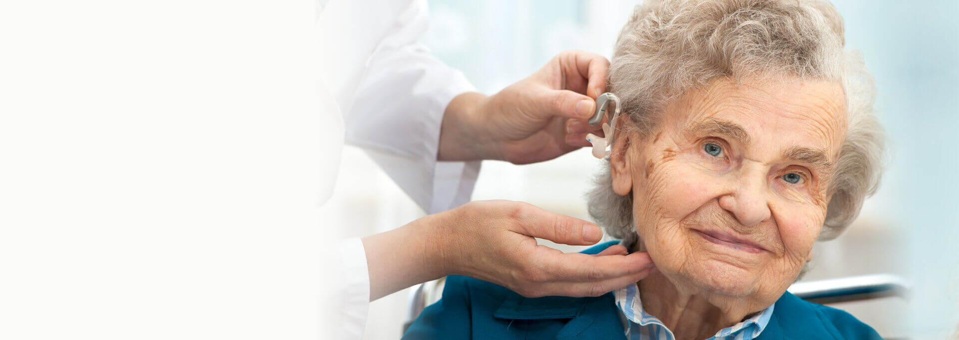 doctor putting an earpiece into a senior woman