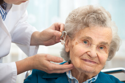 doctor inserting hearing aid in senior woman's ear