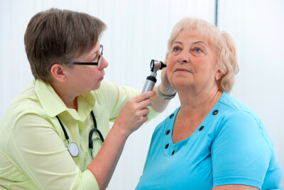 doctor checking the ears of her old woman's patient